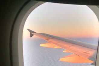 Aircraft wing visible through aicraft window